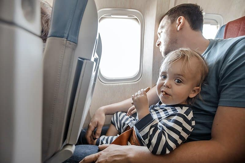 Little adorable boy eating in plane.