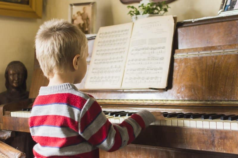 Little boy playing on a piano