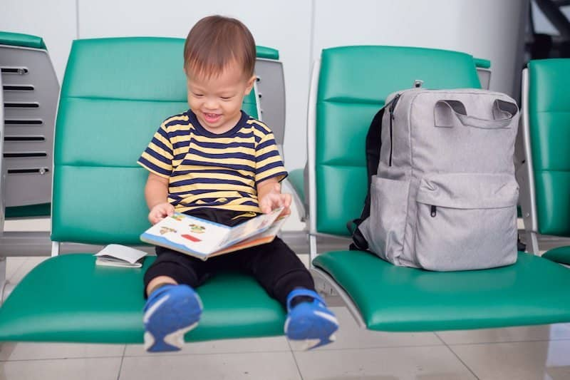 Little boy having fun reading a book while waiting for his flight at gate.
