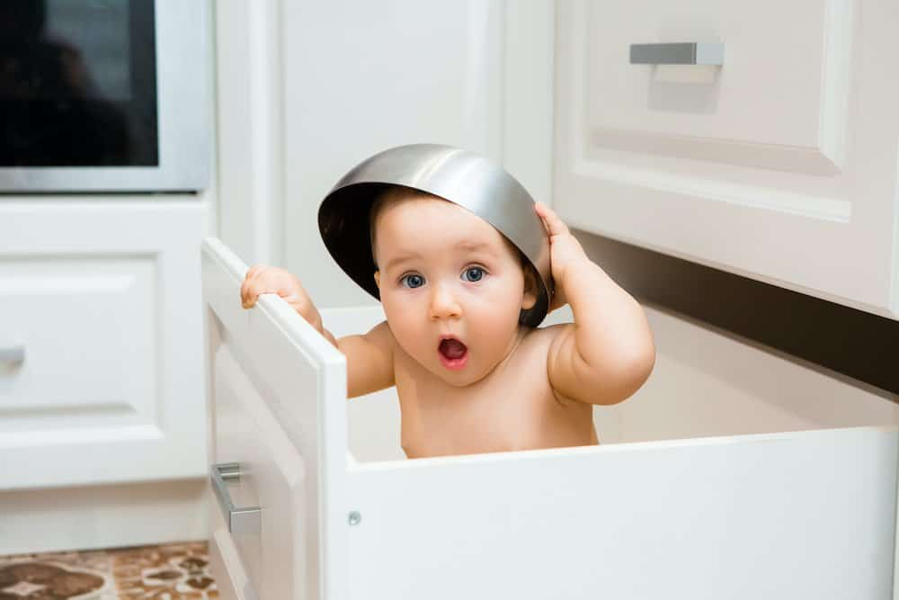 Happy baby girl smiling sitting in kitchen drawer with pans