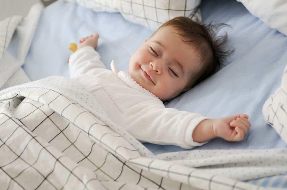 Smiling baby girl lying in bed sleeping