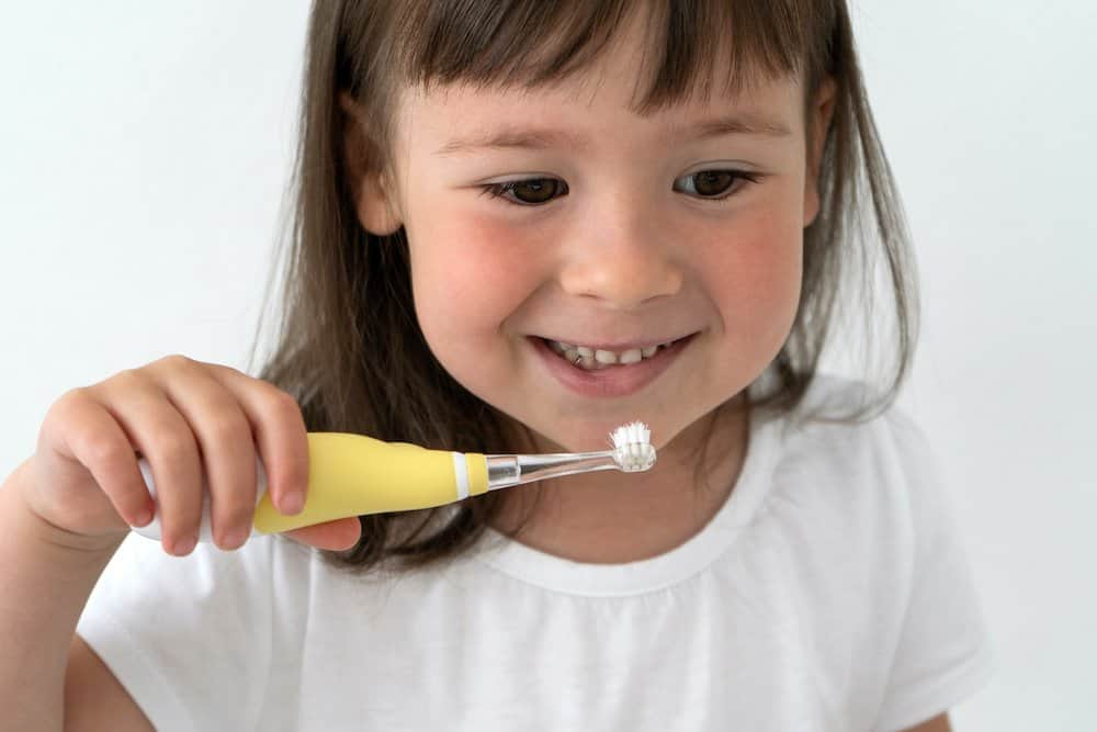 Little girl brushing with electric toothbrush