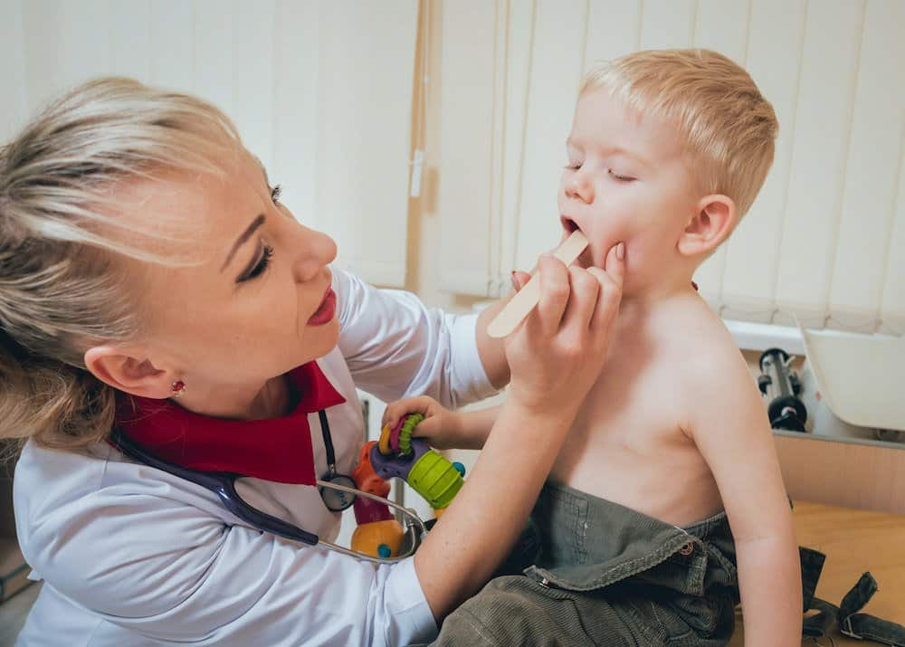 Pediatrician examines toddler for sore throat