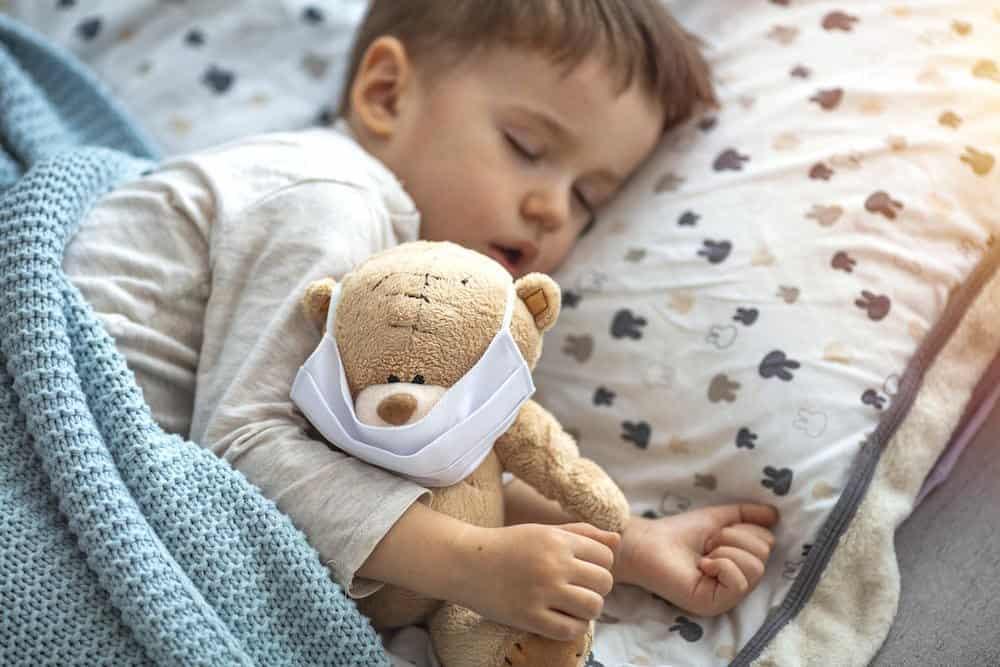 Sick kiddo sleeping with his teddy bear to get better