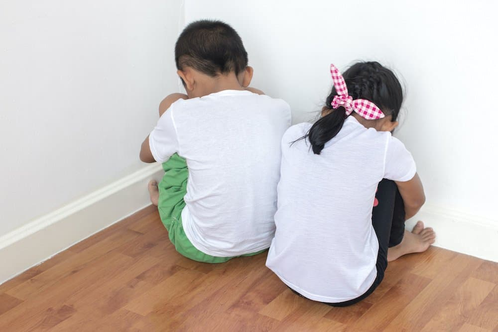 Upset brother and sister in timeout for blaming each other