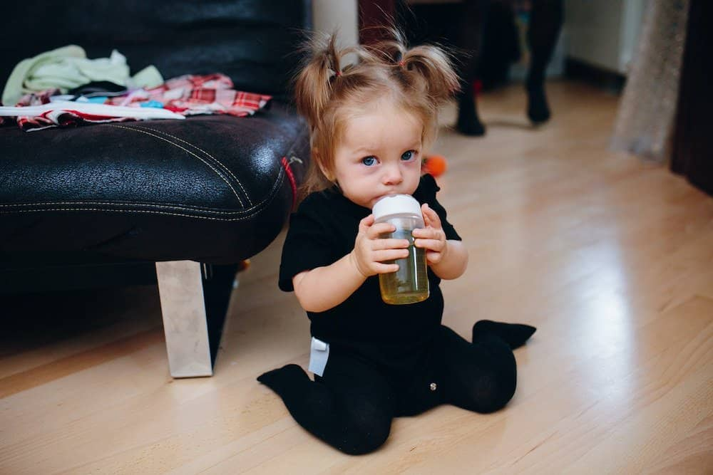 Toddler drinking juice with medicine masked in it