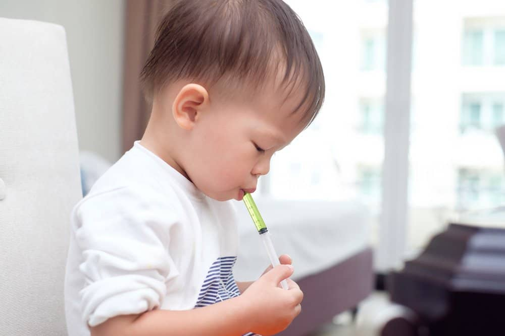 Toddler taking medicine happily with a syringe