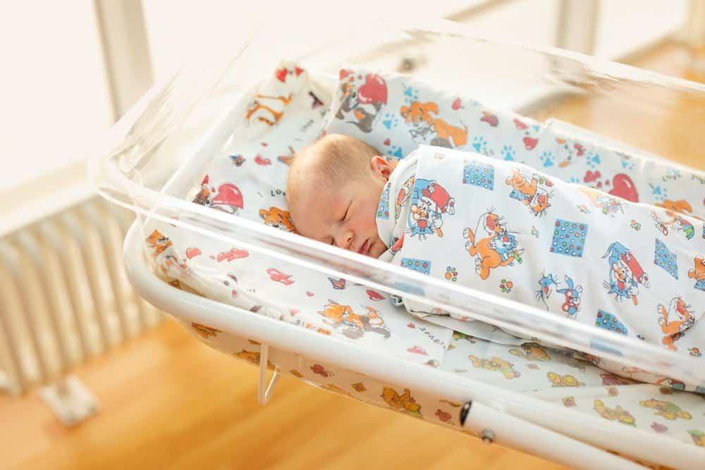 Newborn baby boy sleeping in his cot at the hostpital