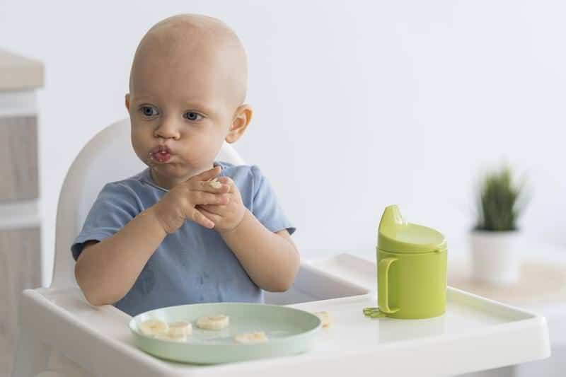 Baby eating finger foods to start eating more solids