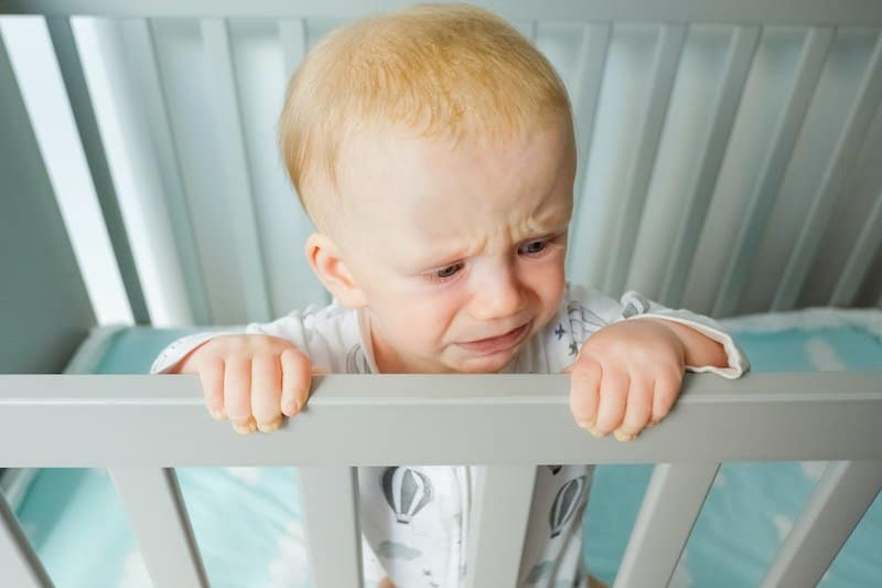 Toddler not happy to sleep in crib anymore might be a sign that they're ready for a toddler bed