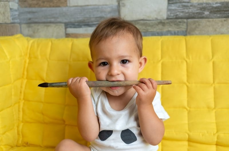 Toddler biting down on a brush stick, and drooling as a result of it, because he is in the teething phase.