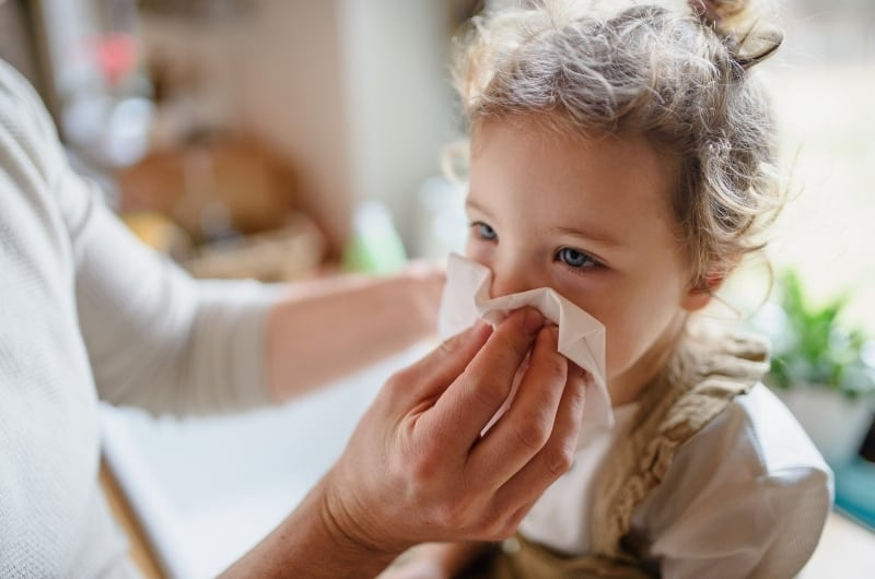 Dad helping his sick toddler girl get better from fever by giving medicine nad helping clean her nose.