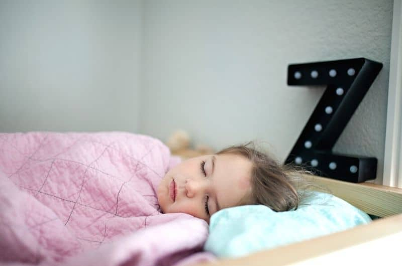 A 4-year-old toddler girl sleeping in her own bed. This is better for her and her parents in many ways.