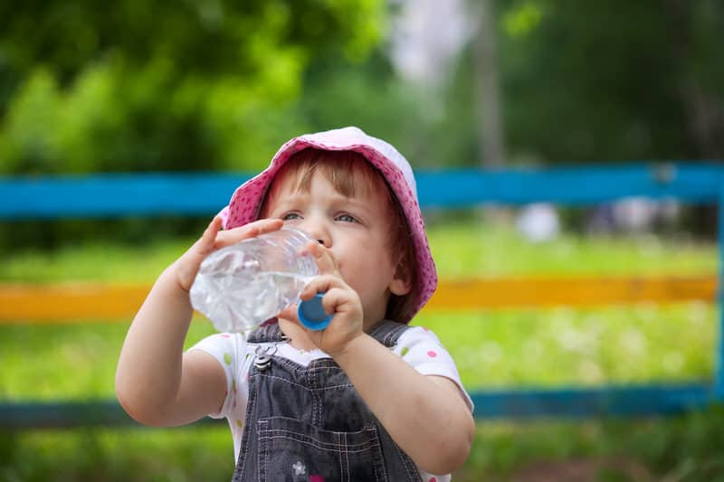 Toddler girl drinking plenty of warm water at home, to help with her constipation relief.