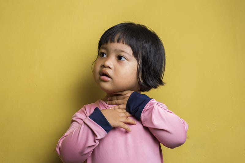 Toddler girl holding her throat, she's drooling excessively because she has tonsillitis.