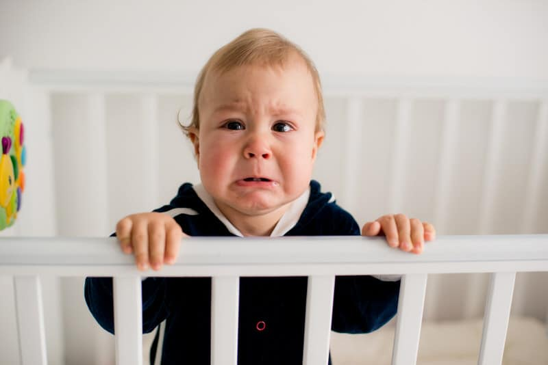 A baby boy crying in crib because he doesn't want to be away from his parents.