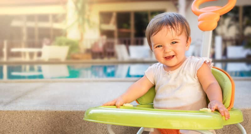 A happy young baby girl sitting in her walker, smiling with lots of energy.