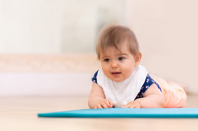 An infant doing tummy time on a yoga mat to help with reflux.