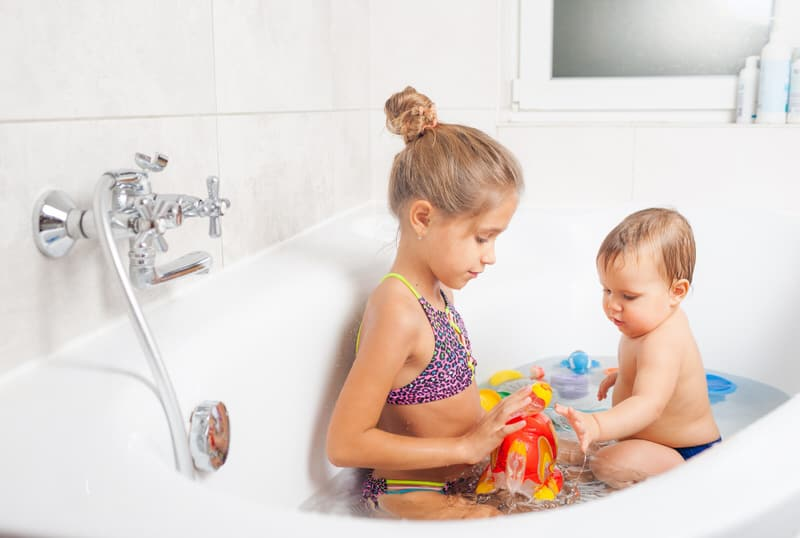 A toddler girl and her baby brother are having fun with play time in the bath tub.