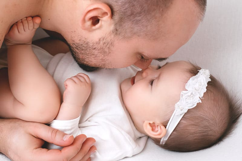 A dad with a stubbly beard is getting close to his infant daughter. Some dads worry that their thick and sharp beard hair might hurt their babies.