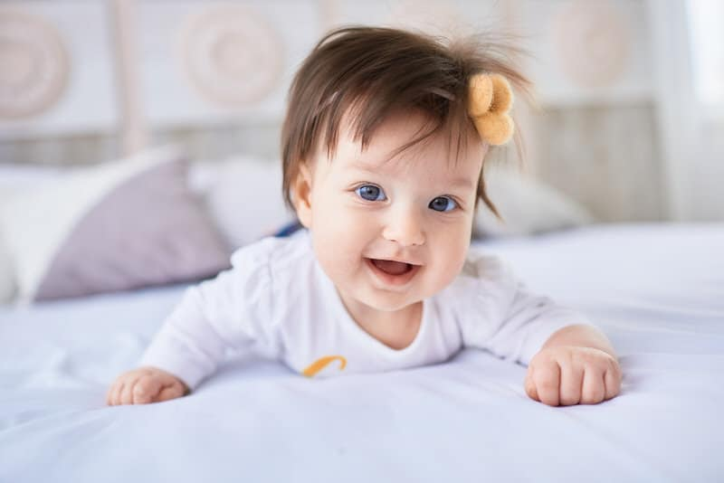 An infant girl is happily laying on her tummy, after some dry shampoo was applied to her hair.