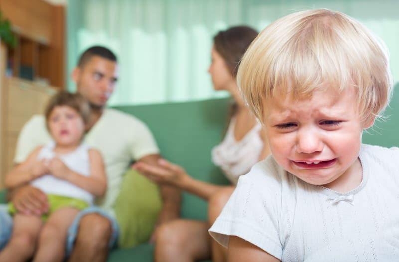 Toddler girl crying because of arguing parents in the background. Bad parenting is creating stress on the child.