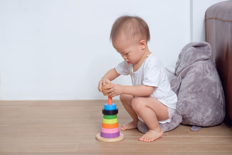 A young toddler is playing with his toys. He has very soft and light hair.