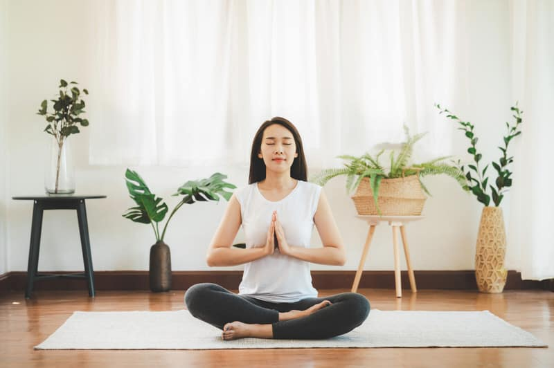 A young Asian mother is meditating at home to help reduce stress in her life.