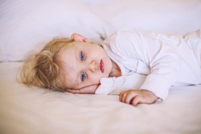 A toddler girl is laying awake on her bed.