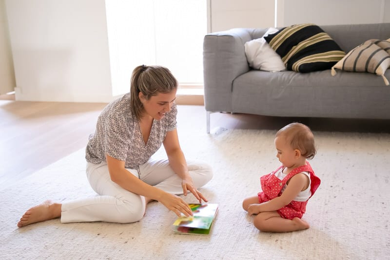 A mom trying to teach her baby daughter two languages, by reading with one and talking to her with the other.