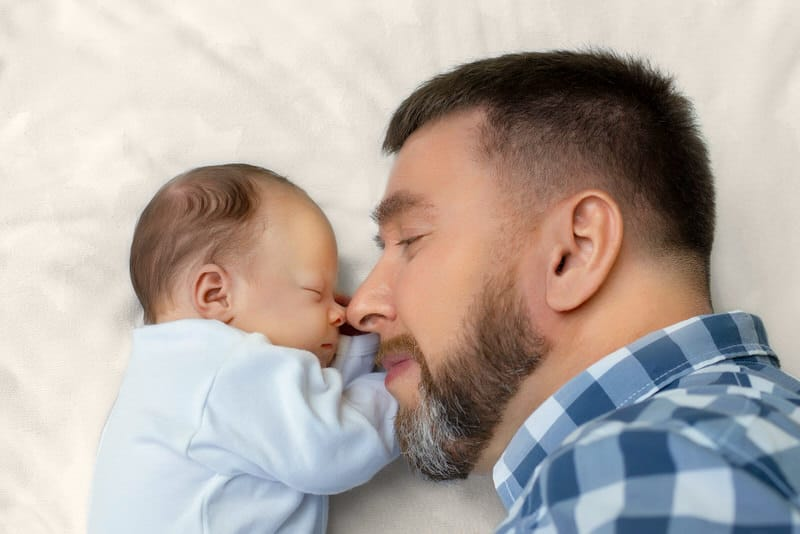 A dad with a beard is laying down happily next to his newborn baby boy.