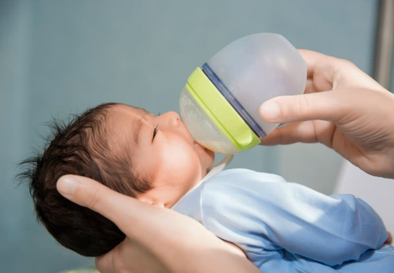 A newborn baby is being bottle fed by her mom.