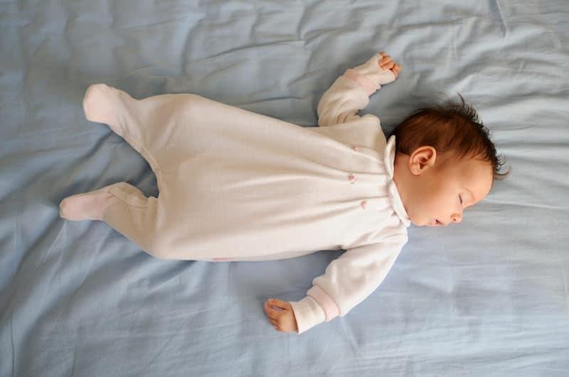 A newborn baby is sleeping in her crib.