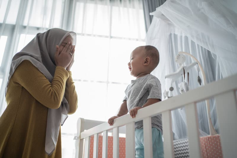 A young mom with her infant baby boy. The baby boy is learning object permanence and will be going through separation anxiety soon as a result of it.