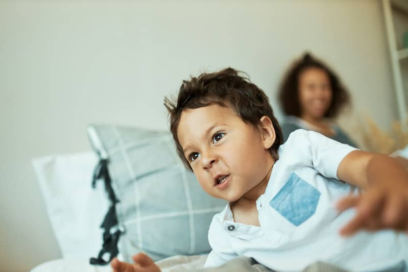 A stubborn toddler is acting naughty, with his mother passively smiling in the background. This uninvolved parent is not supporting her toddler by teaching him a lesson.