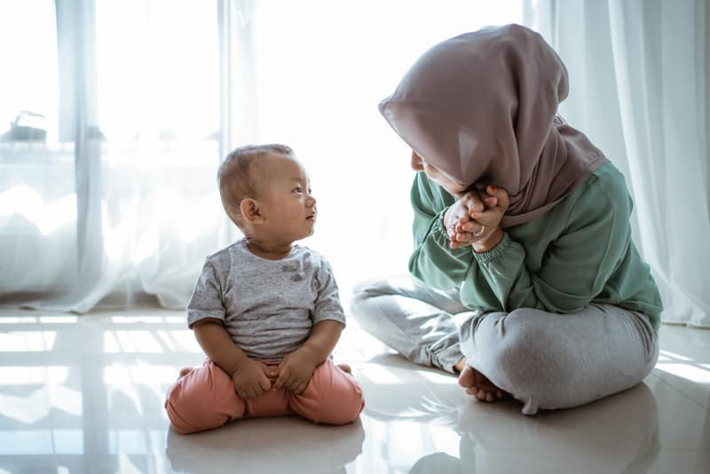 A muslim mom teaching her baby boy two languages at home.
