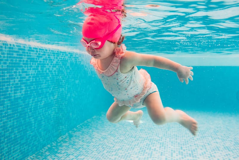 A toddler is getting comfortable being in the water with her new swimming lessons.