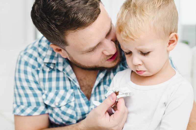 Dad talking to his son about something he did wrong. The dad is using one of the 5 parenting styles to teach his son a lesson.