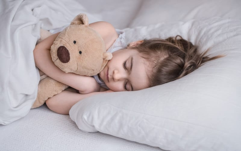 A young toddler girl is sleeping and has a history of night terrors. Parents are watching over her to help her through the process.