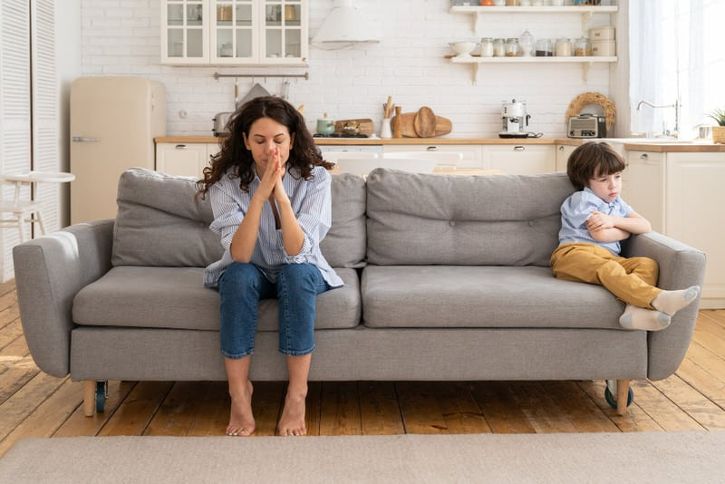 A frustrated and angry mom is sitting on the other side of the sofa, away from her toddler son, who she wants to spank for being bad.