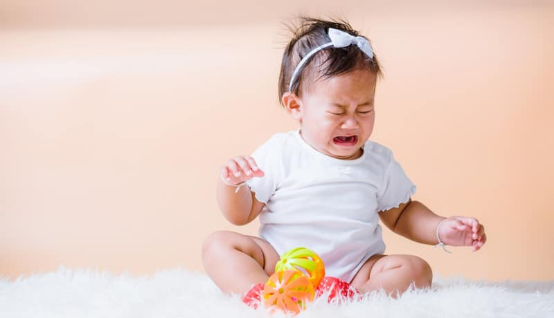 An infant girl is sitting down and crying because of pain from her swollen lymph nodes.