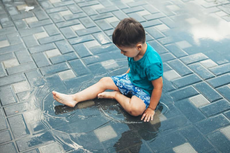 A young toddler boy is being mischievous and is throwing a tantrum by playing in a water puddle.