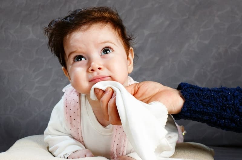 A mom is using a soft baby washcloth to wipe drool from her infant boy's face.