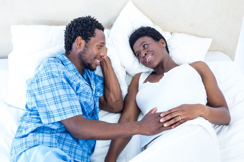 A young and expecting couple are laying on the bed, bonding over the pregnancy.