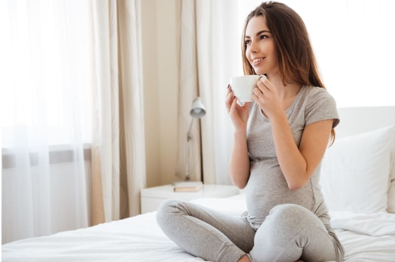 A young pregnant woman is enjoying a cup of coffee on her bed.