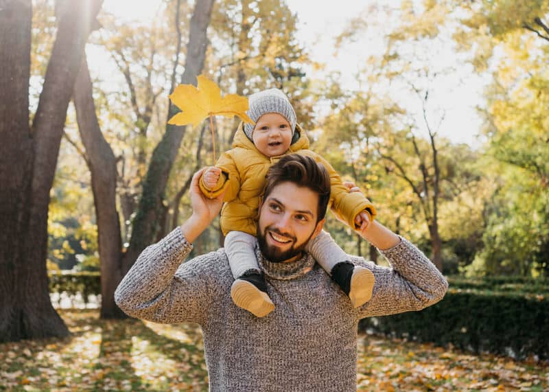 A dad is bonding with his infant daughter by taking her outside for a walk. The little  one is sitting on daddy's shoulders.
