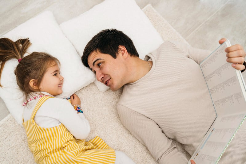 A daughter is laying down with her dad while both are reading a book. The daughter might be displaying signs of Electra complex.