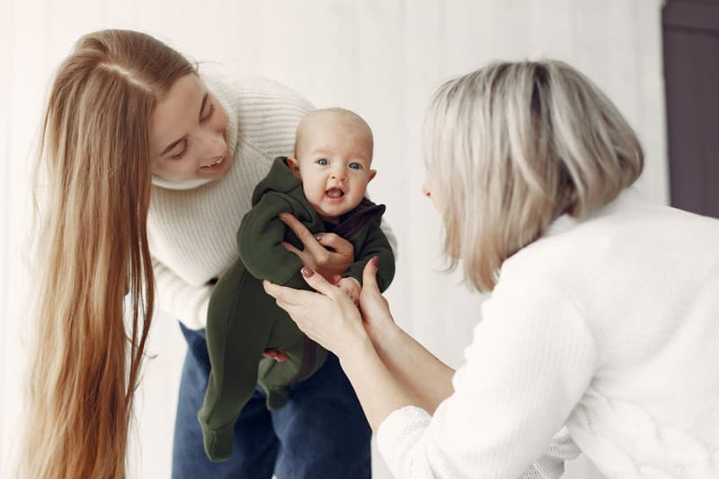 Grandma is interacting with her newborn grandson, and mom has asked that she not kiss the baby.