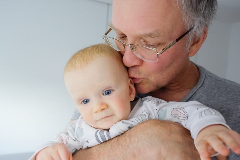Grandpa is kissing his grandson, something mom has asked him not to do. The stubble on his beard can hurt the newborn's sensitive skin.