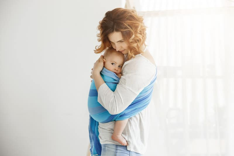 A happy mom is holding her baby boy in a body wrap. She's calm and able to care for her baby because her needs are met and she feels well mentally and physically.